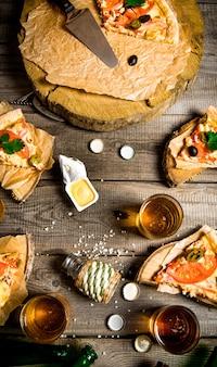 Die pizza party. pizza und bier für vier personen. auf einem holztisch. draufsicht