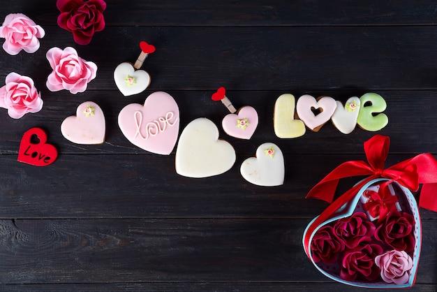 Die plätzchen des valentinsgrußes in form des herzens auf dunklem hölzernem hintergrund