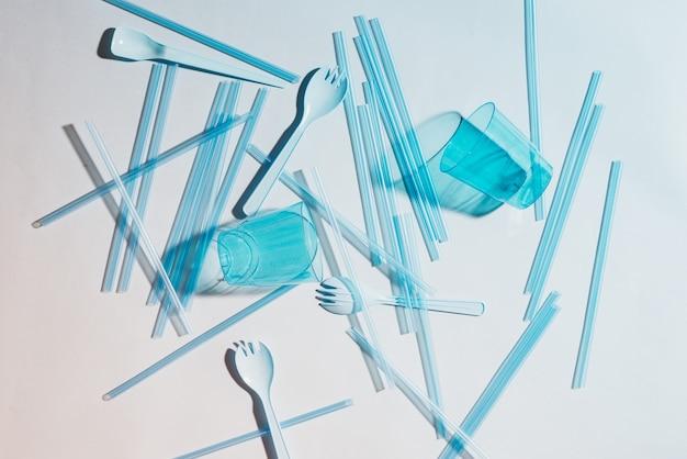 Die plastikstrohhalme belasten die umwelt. plastikmüll, plastikbecher auf hellem hintergrund.