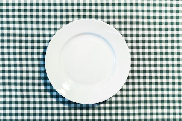 Die platte auf kariertem tischtuch