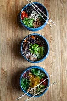 Die poke bowl ist der neueste trend in der lebensmittelindustrie, eine schüssel mit gemüse und lachs auf holzuntergrund