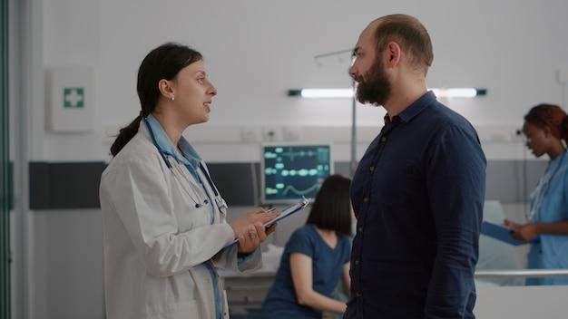 Die praktizierende ärztin diskutiert während der genesungsuntersuchung mit dem besorgten vater über medizinisches fachwissen