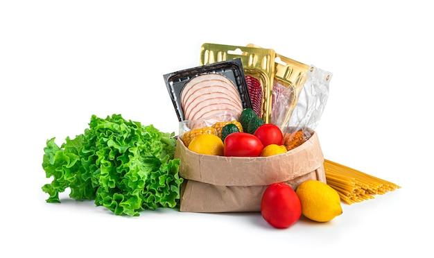 Die produktgruppe ist auf einem weißen schreibtisch isoliert. gemüse, obst, würstchen, nudeln, salat in einer papiertüte, seitenansicht.