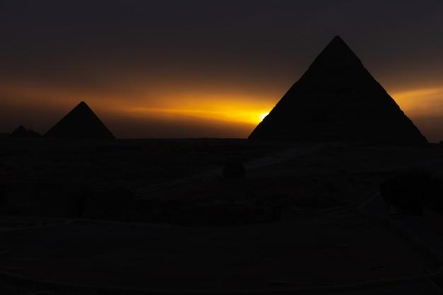 Die pyramiden bei sonnenuntergang, silhouetten im dunkeln in gizeh, ägypten.