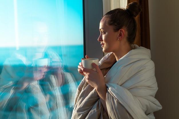 Die recht junge frau, die in eine decke eingewickelt wird, steht nahes fenster und genießt kaffee des ersten morgens auf sonnenschein. ein frühes aufwachen und der beginn eines neuen tages