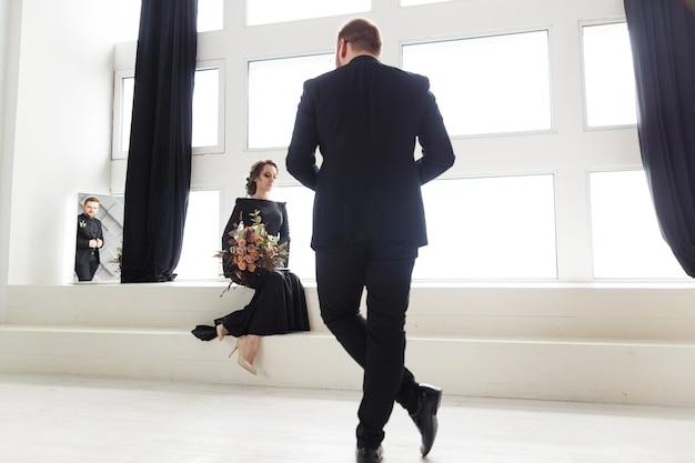 Die reflexion des bräutigams im spiegel. braut, die auf treppe im weißen studio nahe fenster sitzt