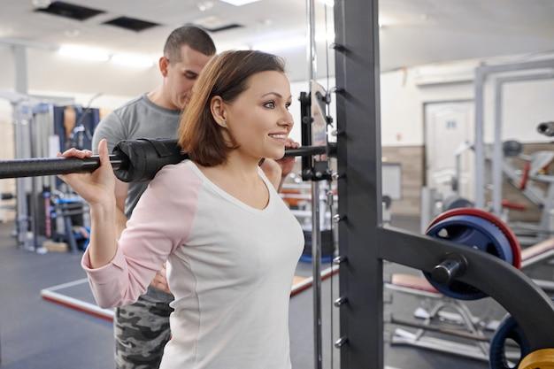 Die reife frau, die sport tut, trainiert mit persönlichem trainer an der turnhalle.