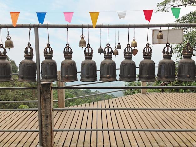 Die reihen von schablonierten thailändischen tempelglocken hingen entlang der hölzernen bahn mit natur- und himmelhintergrund