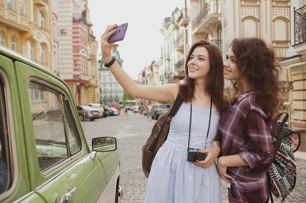 Die reizenden frauen, die selfies beim besichtigen in der stadt nehmen, kopieren raum
