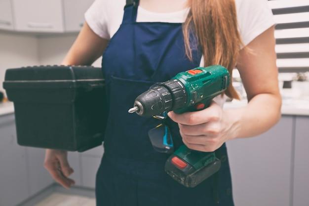 Die reparaturfrau in arbeitskleidung im haus mit werkzeugkasten und anderen geräten in der hand