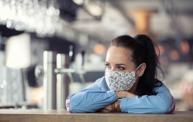 Die restaurantbesitzerin mit gesichtsmaske denkt über die zukunft ihres geschäfts nach, die sich an die bar lehnt.