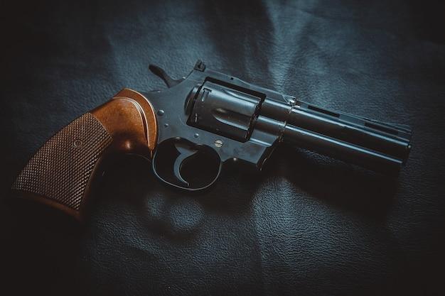 Die revolverpistole ruht auf einem schwarzen lederblatt