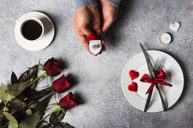 Die romantische abendessengedeck-mannhand des valentinstags, die verlobungsring im kasten hält, heiraten mich