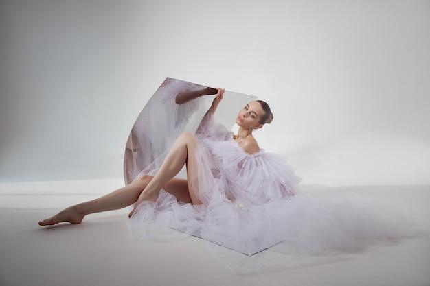 Die romantische schönheitsfrau in einem hellen transparenten kleid spiegelt sich in einem flexiblen spiegel wider, der auf dem boden sitzt. perfekter körper