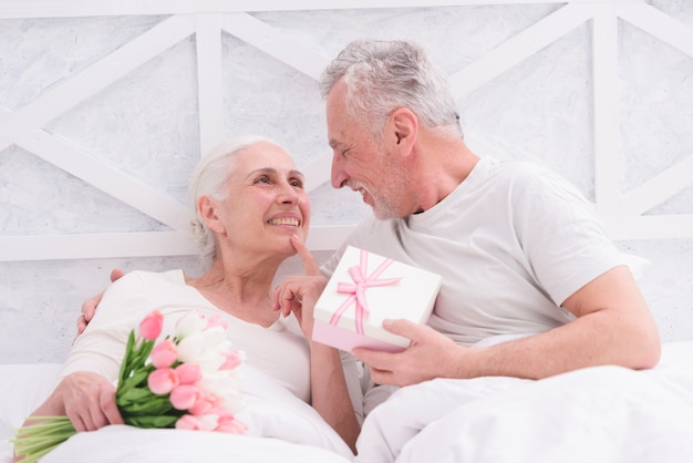 Die romantischen älteren paare, die einander halten blumenstrauß und geschenkbox herein betrachten, hatten
