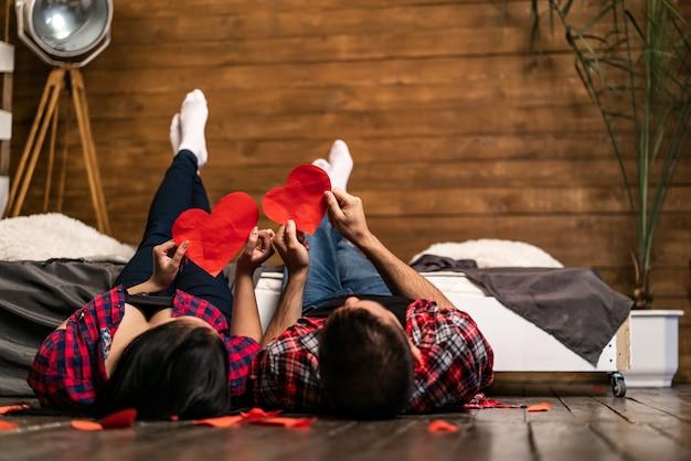 Die romantischen paare, die auf bretterboden nahe dem bett liegen und rote herzen halten, formen zu hause.