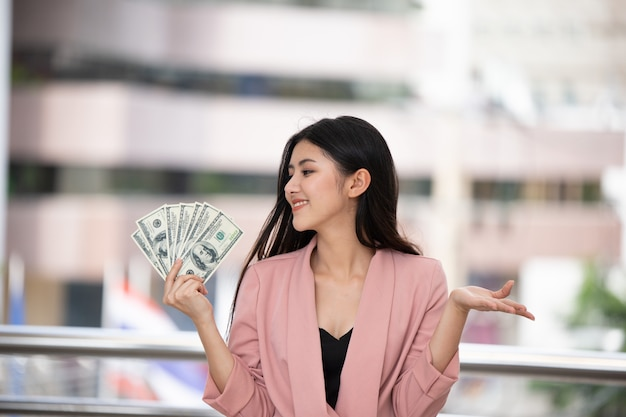 Die rosa klage der jungen asiatinabnutzung, die dollar gegen unscharfen stadthintergrund sehr glücklich hält