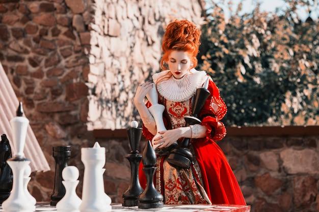 Die rote königin spielt schach. rothaarige frau in einem schicken weinlesekleid.