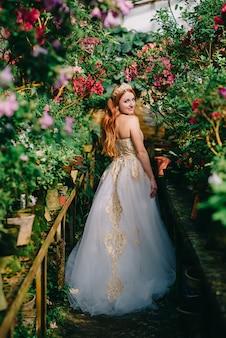 Die rothaarige frau im luxuriösen kleid steht zwischen blühenden azaleenblüten