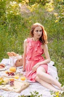 Die rothaarige frau im rosa kleid mit einem glas orangensaft.