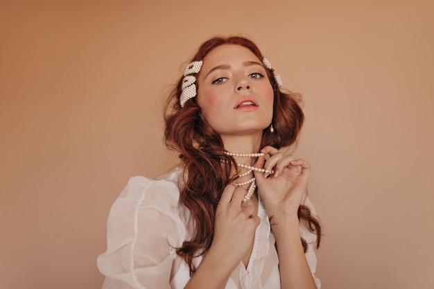 Die rothaarige frau mit den rosa wangen spielt mit ihrer perlenkette. dame in der klassischen weißen bluse, die unten in die kamera schaut.