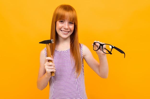 Die rothaarige frau nimmt die brille ab und bricht die linsen mit einem hammer