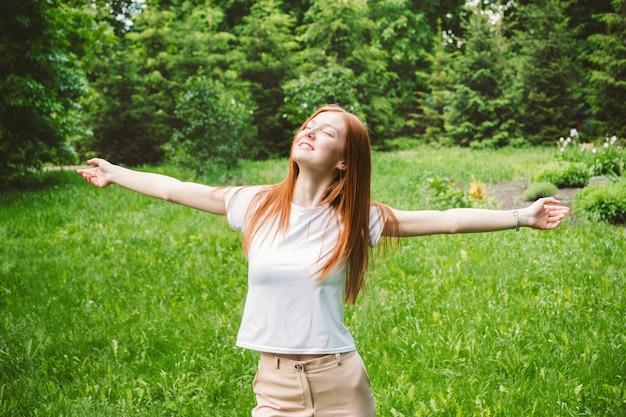 Die rothaarige geschäftsfrau genießt urlaub im park