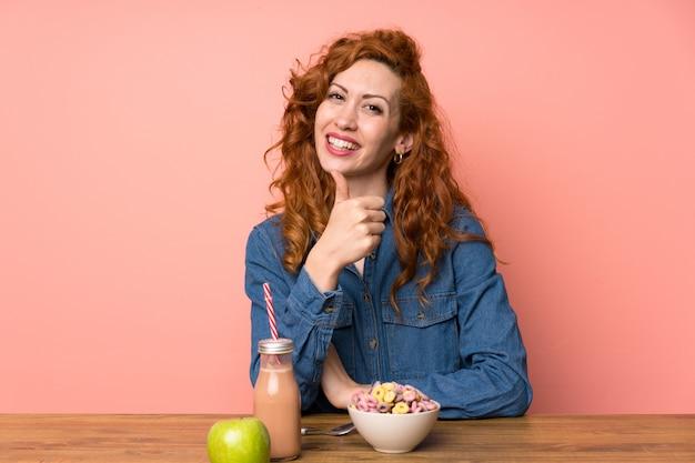 Die rothaarigefrau, die frühstückskost aus getreide und obst gibt daumen hoch isst, gestikulieren