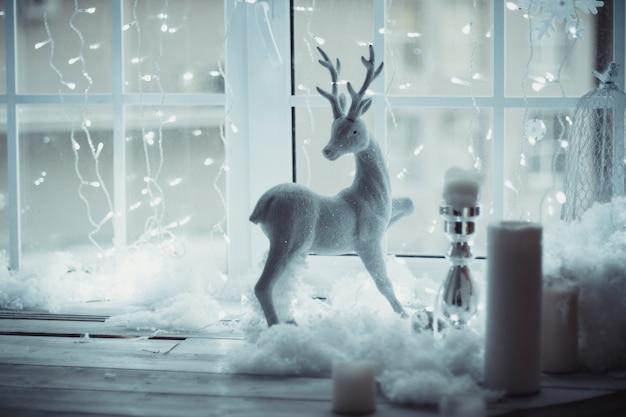 Die rotwildzahl, die am fenster auf dem hintergrund des weihnachtsdekors steht. warten auf ein wunder