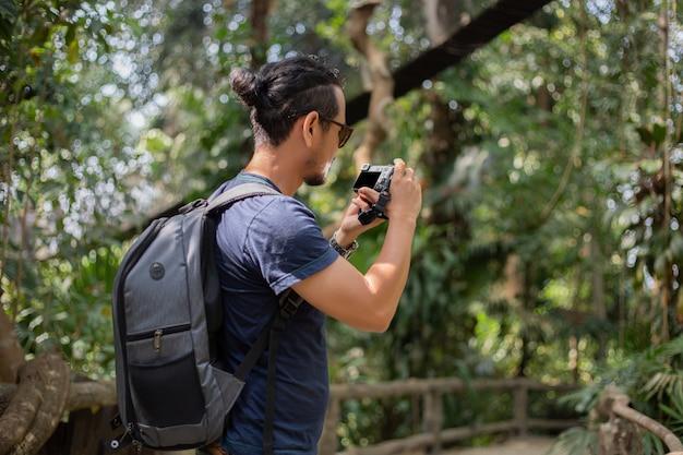 Die rucksäcke und der reisende der asiatischen männer, die zusammen gehen und glücklich sind, machen foto auf wald, entspannen sich zeit auf feiertagskonzeptreise