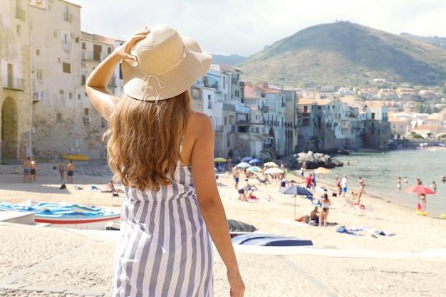 Die rückansicht der jungen frau geht zum strand der altstadt von cefalu in sizilien hinunter