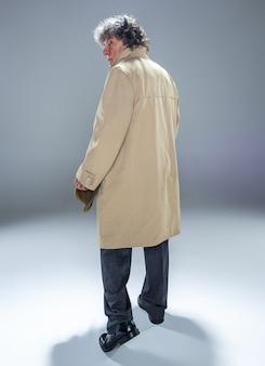 Die rückansicht des älteren mannes im umhang als detektiv oder mafia-chef. studioaufnahme auf grau im retro-stil. reifer mann mit hut und koffer