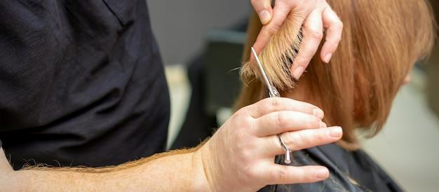 Die rückansicht des friseurs schneidet rotes oder braunes haar zur jungen frau im schönheitssalon. haarschnitt im friseursalon. weicher fokus