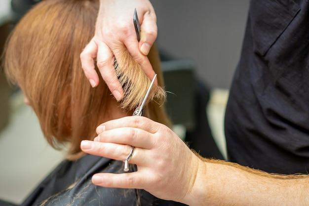 Die rückansicht des friseurs schneidet rotes oder braunes haar zur jungen frau im schönheitssalon. haarschnitt im friseursalon