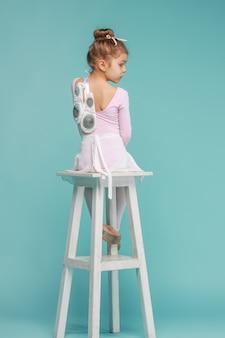 Die rückansicht des kleinen mädchens als balerina-tänzerin, die auf weißem holzstuhl im blauen studio sitzt
