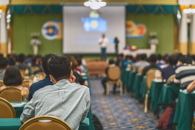 Die rückansicht des publikums, das die lautsprecher hört, präsentiert die rutsche auf der bühne im konferenzraum