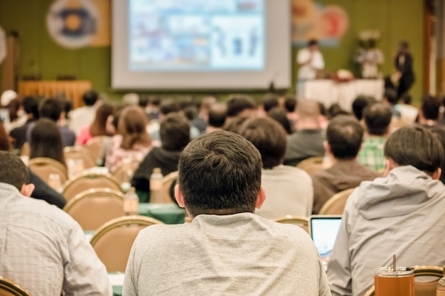 Die rückansicht des publikums, das die lautsprecher hört, präsentiert die rutsche auf der bühne