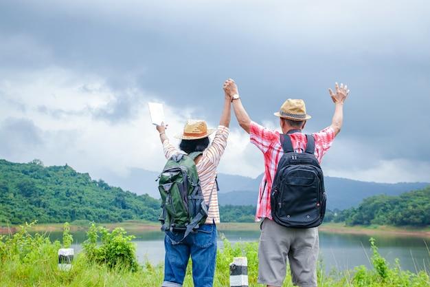 Die rückansicht eines älteren ehepaares im ruhestand mit einem rucksack, um die natur zu genießen. das konzept des glücks in der familie, der älteren gemeinschaft