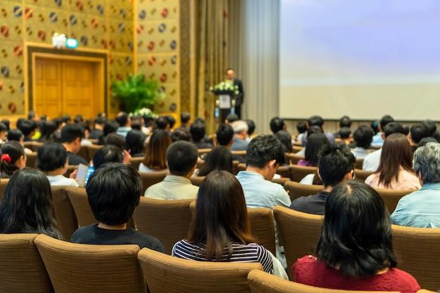 Die rückseite des publikums hört den sprecher mit podium auf der bühne in der konferenzhalle