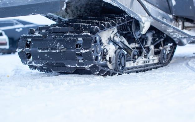 Die rückseite des schneemobils im winter. mit einem schneemobil im schnee fahren. hinterradaufhängung eines schneemobils