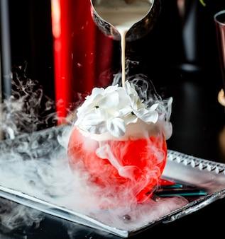 Die sahne wird in ein rundes glas mit einem roten cocktail gegossen, der mit sahne und blumen garniert ist