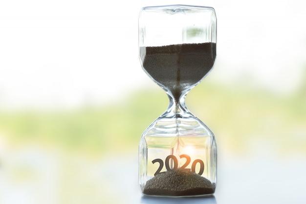 Die sanduhr auf dem tisch zeigt an, dass die zeit des jahres 2020 beginnt.
