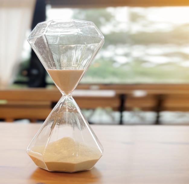 Die sanduhr im mangel an klarem glas schön, auf dem tisch im café gelegen