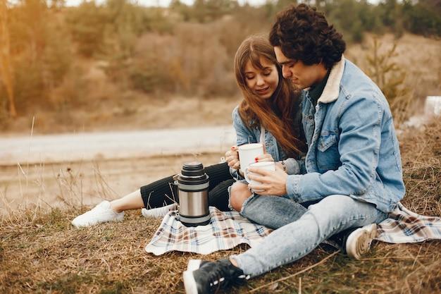 Die sanften und stilvollen paare, die im herbstpark sitzen und einen tee trinken
