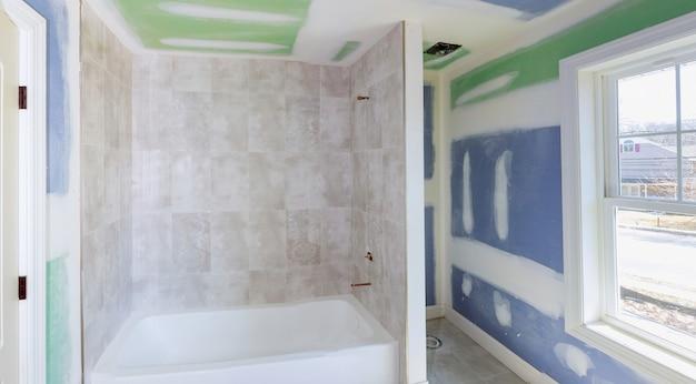 Die sanierung des bades schreitet voran, wenn die trockenmauer geglättet wird und nähte und schrauben mit klebeband bedeckt werden