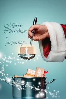 Die santa-hand, die eine schöpfkelle oder einen küchenlöffel hält und zur weihnachtszeit auf blauem studiohintergrund bereit ist. collage und konzeptbild