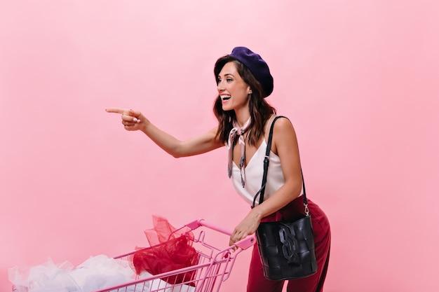 Die schelmische frau zeigt mit dem finger in die ferne und nimmt den einkaufswagen. lächelnde dame in der weißen bluse und in der hose auf rosa hintergrund.