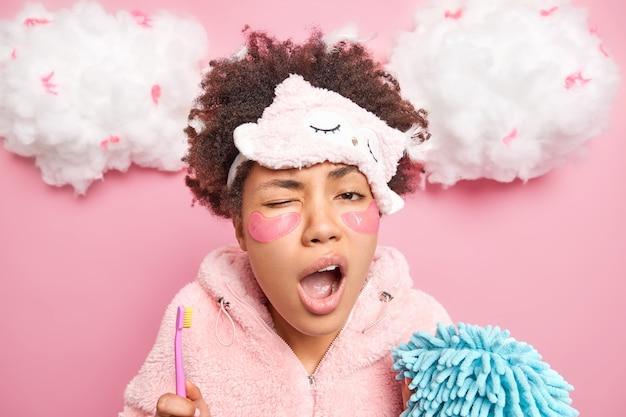 Die schläfrige, lockige afroamerikanische frau unterzieht sich morgens täglichen hygienemaßnahmen. sie hält zahnbürste und badeschwamm gähnt mit weit geöffnetem mund