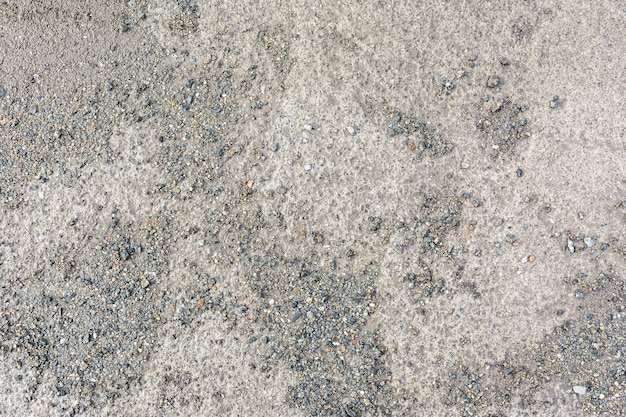 Die schlammige betonstraße ist mit feinen kieskrümeln bedeckt