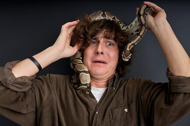 Die schlange kletterte auf den kopf des mannes, der mann hat noch mehr angst, er fühlt gefahr, steht verängstigt und verängstigt da, verängstigt
